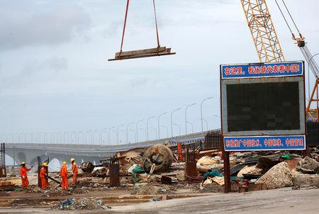 FILE PHOTO: Constrcution workers work at a site as the China-funded Sinamale bridge is seen in Male, Maldives September 18, 2018. REUTERS/Ashwa Faheem/File Photo