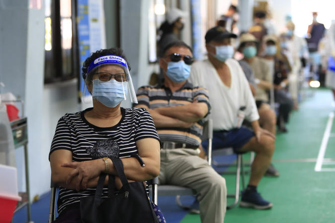 Elderly people and other citizens wait for vaccination against the Coronavirus at a vaccination centre, following an outbreak with a surge in the number of domestic infections and deaths, in Taipei, Taiwan, 5 July 2021. (Photo by Ceng Shou Yi/NurPhoto via Getty Images)