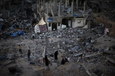 Palestinians sit atop the ruins of their house which witnesses said was destroyed during the Israeli offensive, in the east of Gaza City
