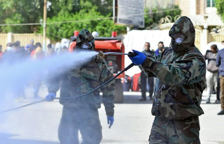 Civil defence teams disinfect a seminary in the Shiite shrine city of Najaf where Islamic students are believed to have come in contact with Iraq's first confirmed case of novel coronavirus