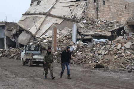 Rebel fighters walk near damaged buildings in al-Rai town, northern Aleppo countryside, Syria December 30, 2016. REUTERS/Khalil Ashawi