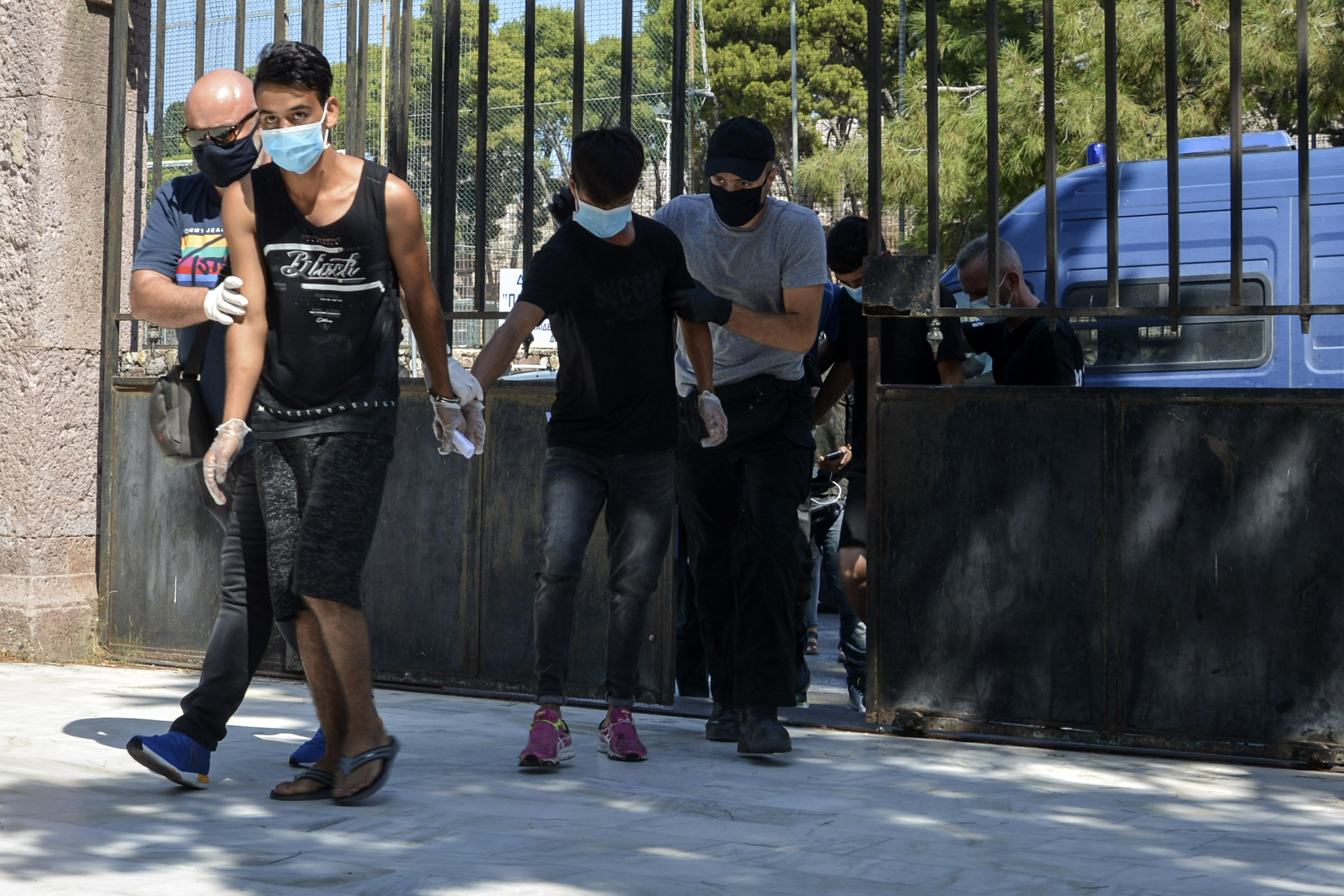 Suspects, all from Afghanistan escorted by plain clothes policemen and wearing face masks, arrive at a court in Mytilene, the capital of the northeastern Aegean island of Lesbos, Greece, Wednesday, Sept. 16, 2020. The government says the fires in Moria refugee camp were set deliberately by the Afghan migrants protesting a coronavirus lockdown, and authorities on Tuesday announced the arrests of six suspect, include two 17-year-olds, in the case. (AP Photo/Panagiotis Balaskas)