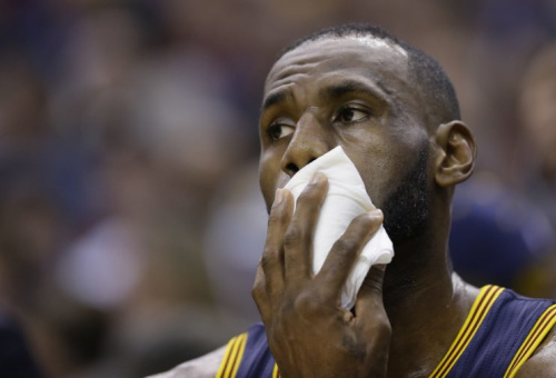 LeBron James rests on the bench during a February game this past season. (AP)