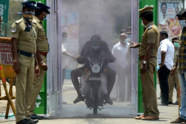 A motorist rides through a disinfection tunnel in Chennai, India (AFP Photo/Arun SANKAR )