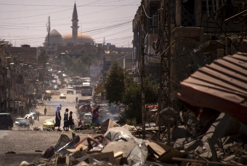 Iraqis walk on a damaged street in west Mosul on July 12, 2017 after the government announced the recapture of the city from the Islamic State group (AFP Photo/FADEL SENNA)