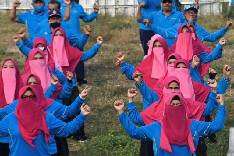 Female civil servants do morning exercises in Lombok, wearing veils instead of masks (AFP Photo/Moh El Sasaky)