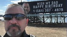 Dad bombarded with birthday phone calls after sons prank him with billboard featuring his phone number