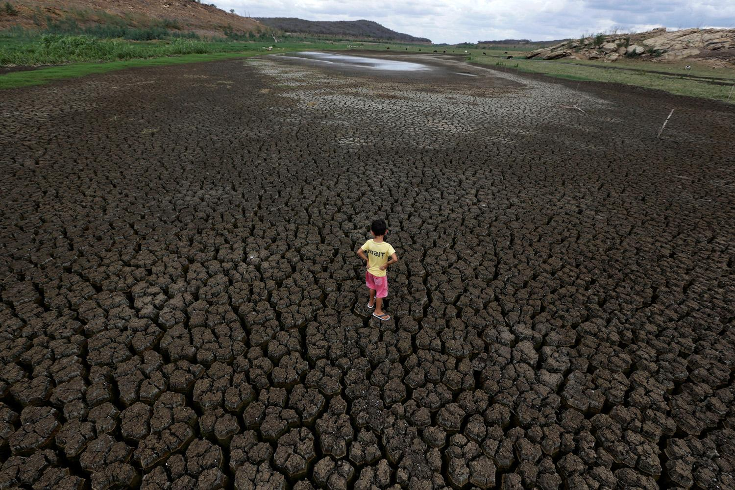 <p>Natan Cabral, 5, stands on the cracked bed of the Boqueirao Reservoir in the Metropolitan Region of Campina Grande, Paraiba state, Brazil, Feb. 13, 2017. (Photo: Ueslei Marcelino/Reuters) </p>