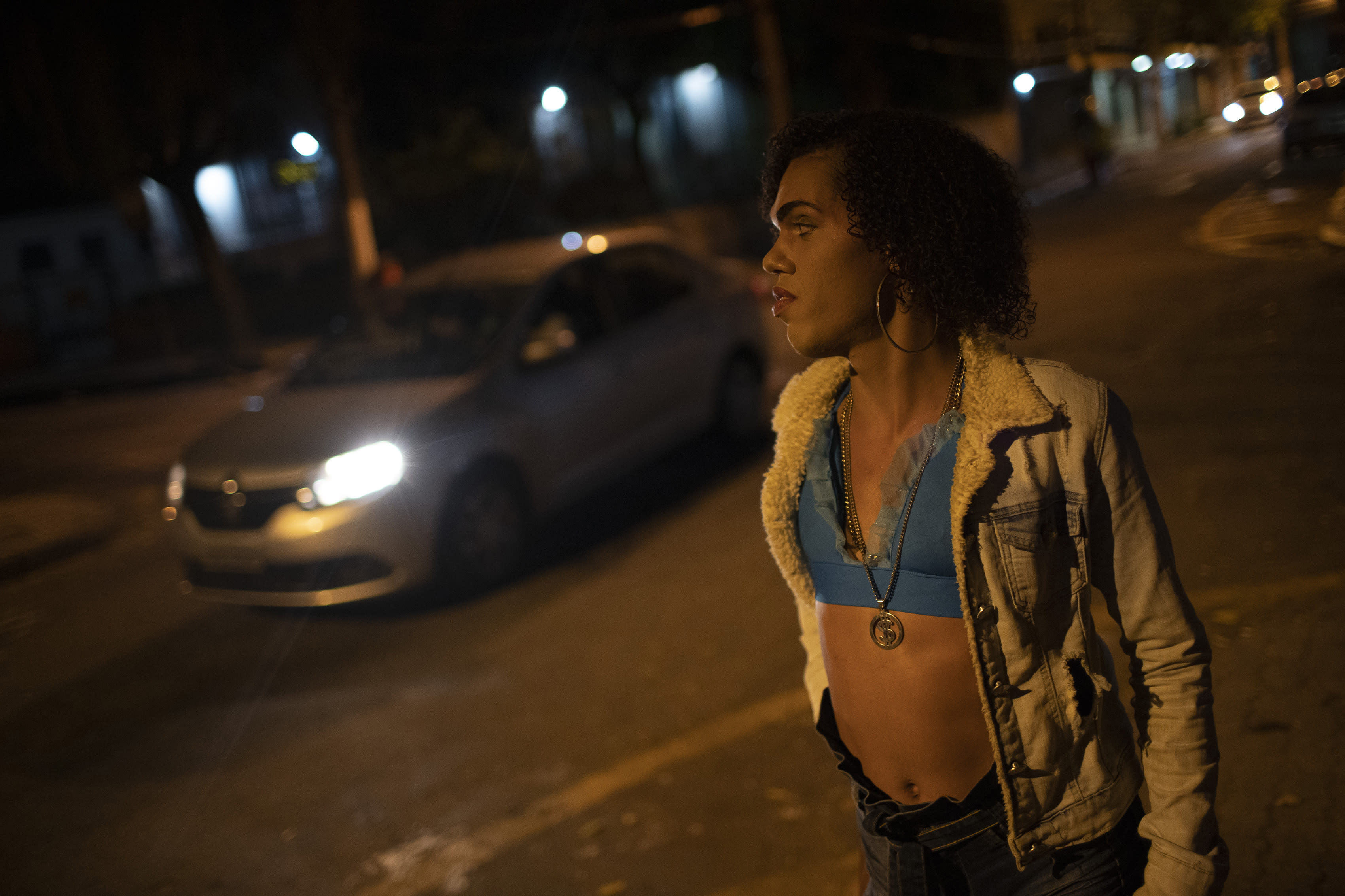 """Transgender sex worker Alice Larubia waits for customers in Niteroi, Brazil, Saturday, June 27, 2020, amid the new coronavirus pandemic. She keeps hand sanitizer in her purse and wears a mask on public transport, but said she can't while working. She earns around $15 per night, less than half her payday before the onset of the outbreak. """"I'm scared,"""" she said. """"I know I'm at risk."""" (AP Photo/Silvia Izquierdo)"""