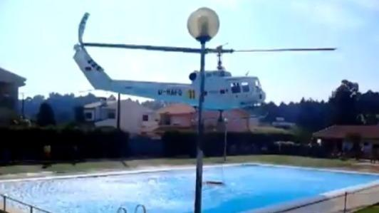 Helicopter refills water bucket from a public pool