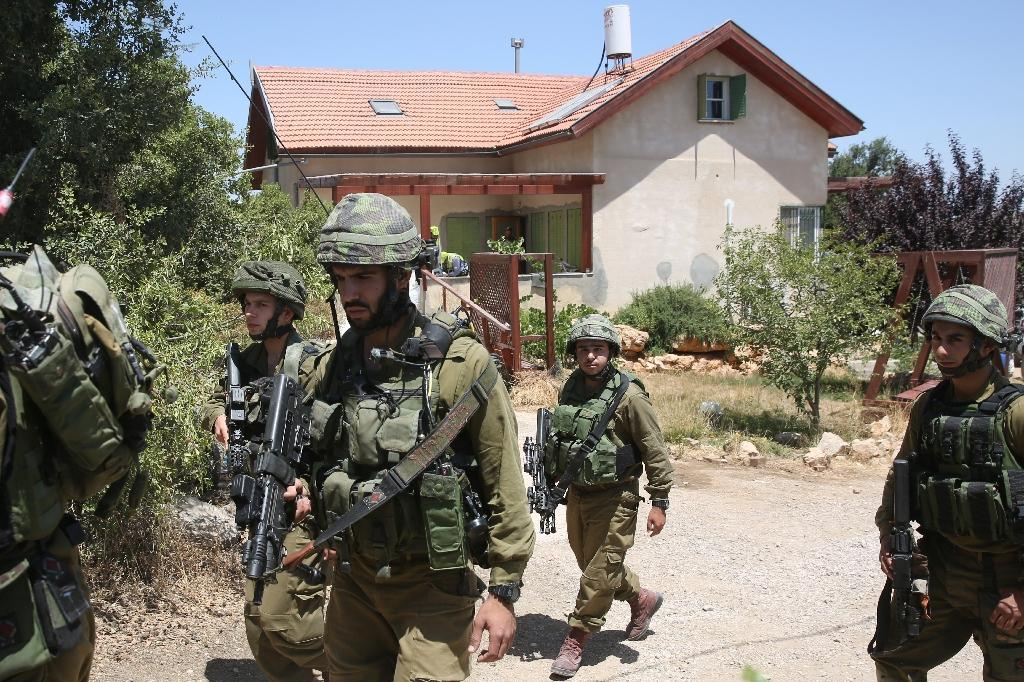 Israeli soldiers stand guard outside a house in the Jewish West Bank settlement of Kiryat Arba where a 13-year-old Israeli girl was fatally stabbed, on June 30, 2016 (AFP Photo/Menahem Kahana)