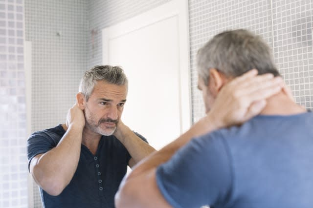Mature man looking in bathroom mirror