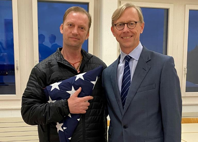 US Navy veteran Michael White (L) holding a folded US flag poses with US Special envoy to Iran Brian Hook at Zurich Airport in Zurich, Switzerland, on June 4, 2020 after his release from Iran (AFP Photo/-)