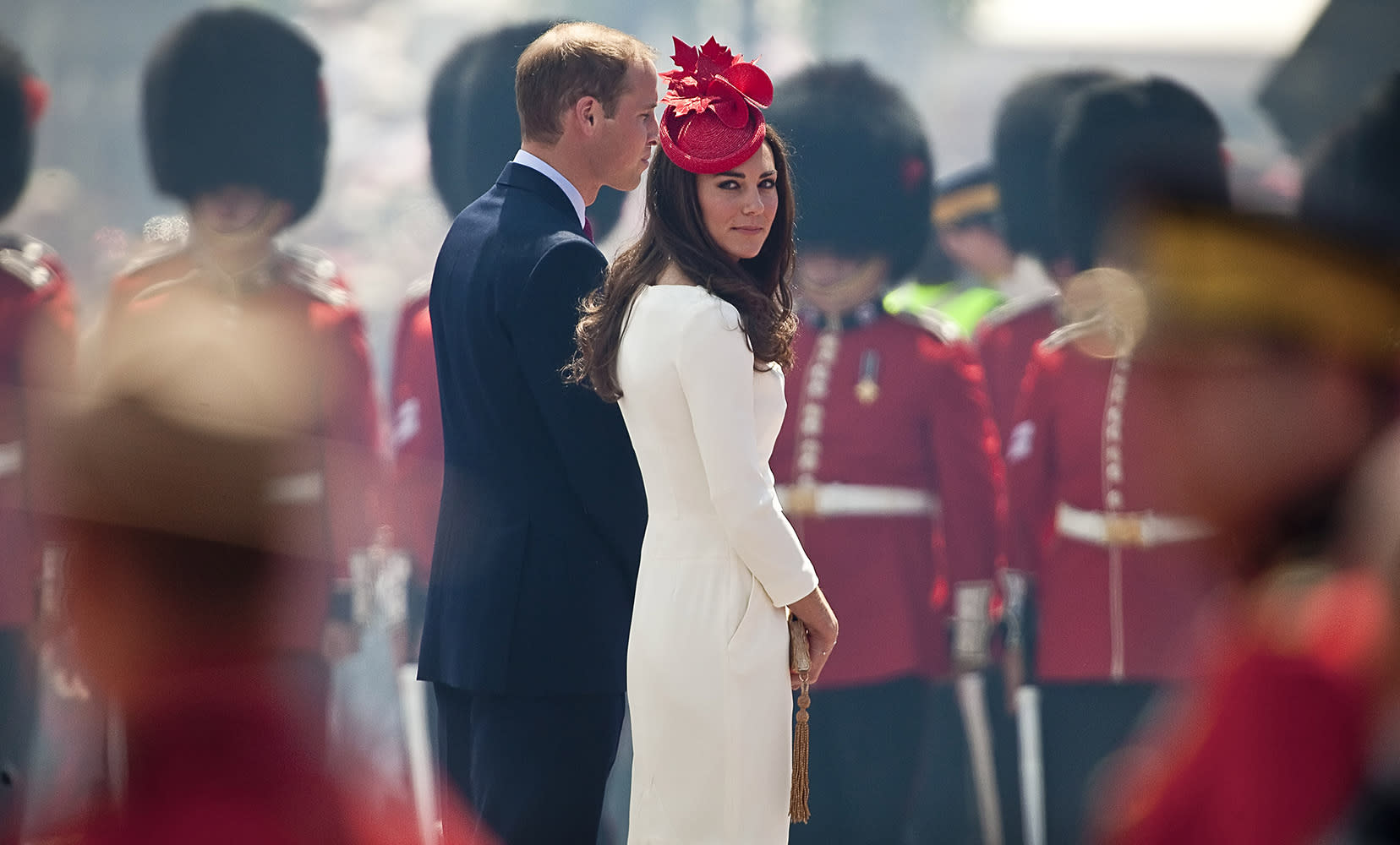 Kate looks over her shoulder as she and Wills attend Canada Day celebrations in Ottowa. She was wearing a white Reiss dress with bold red accents in her fascinator and heels.