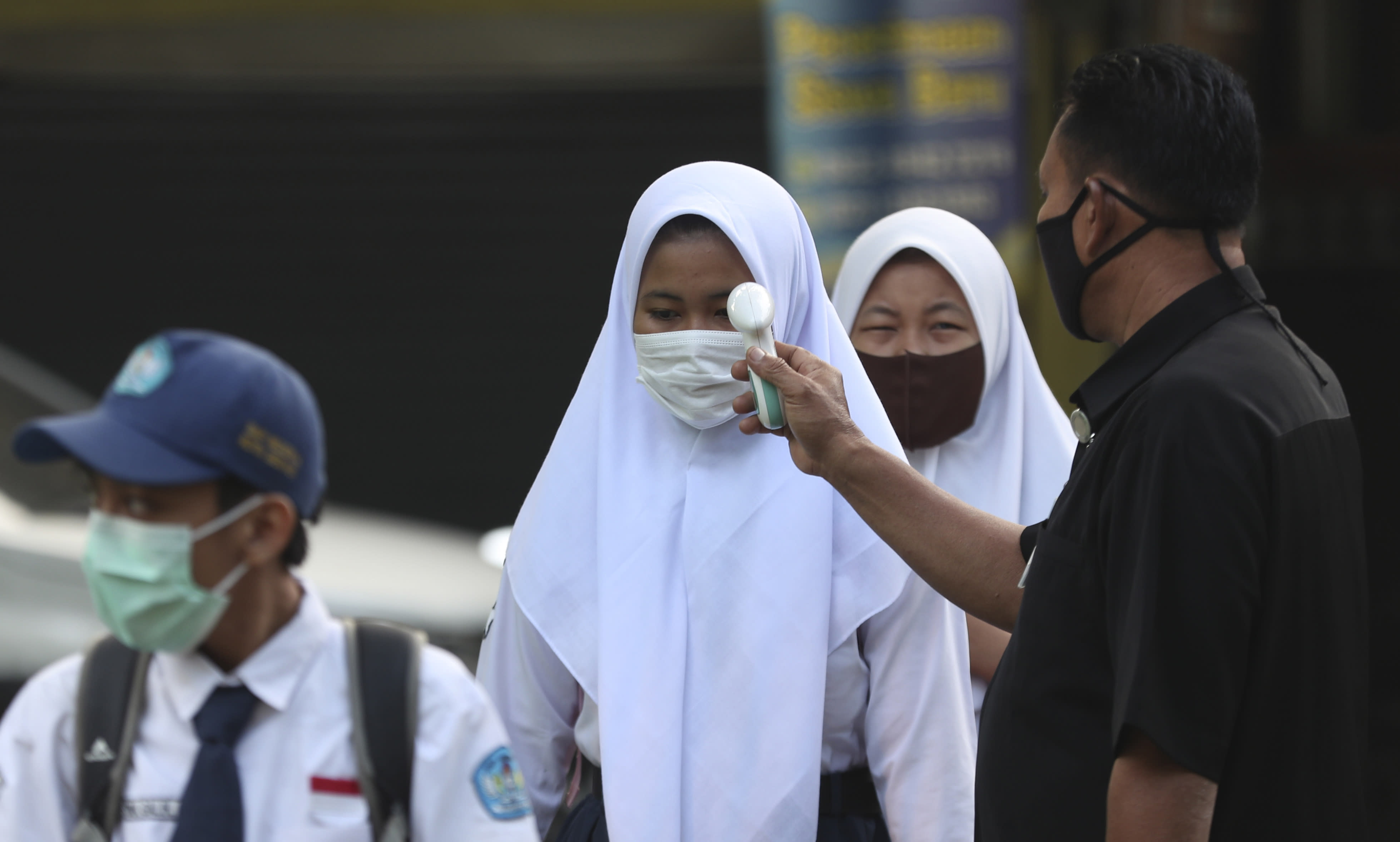 A security guard checks the body temperature of a student before entering a school amid coronavirus outbreak during the first day of school reopening at a state high school in Bekasi on the outskirts of Jakarta, Indonesia July 13, 2020. (AP Photo/Achmad Ibrahim)