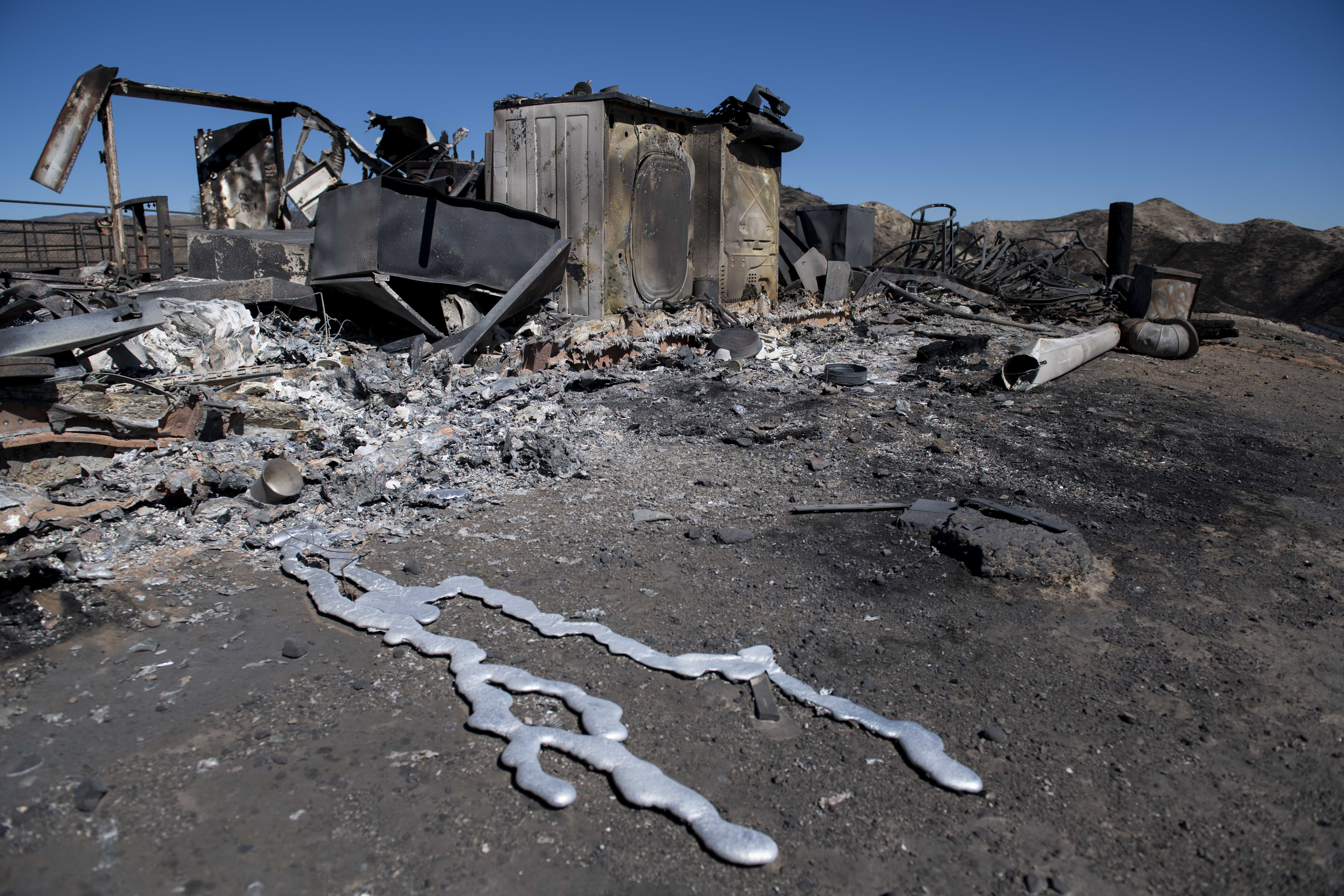 Debris from a hilltop home smolders after being burned by the Tick Fire Thursday Oct. 25 2019 in Santa Clarita Calif. An estimated 50,000 people were under evacuation orders in the Santa Clarita area north of Los Angeles as hot dry Santa Ana winds