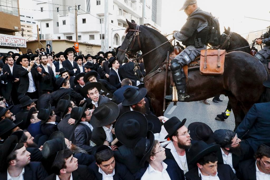Mounted members of the Israeli security forces try to disperse ultra-Orthodox Jews who are blocking a road during a demonstration against Israeli army conscription in the Israeli city of Bnei Brak near Tel Aviv on March 22, 2018 (AFP Photo/JACK GUEZ)