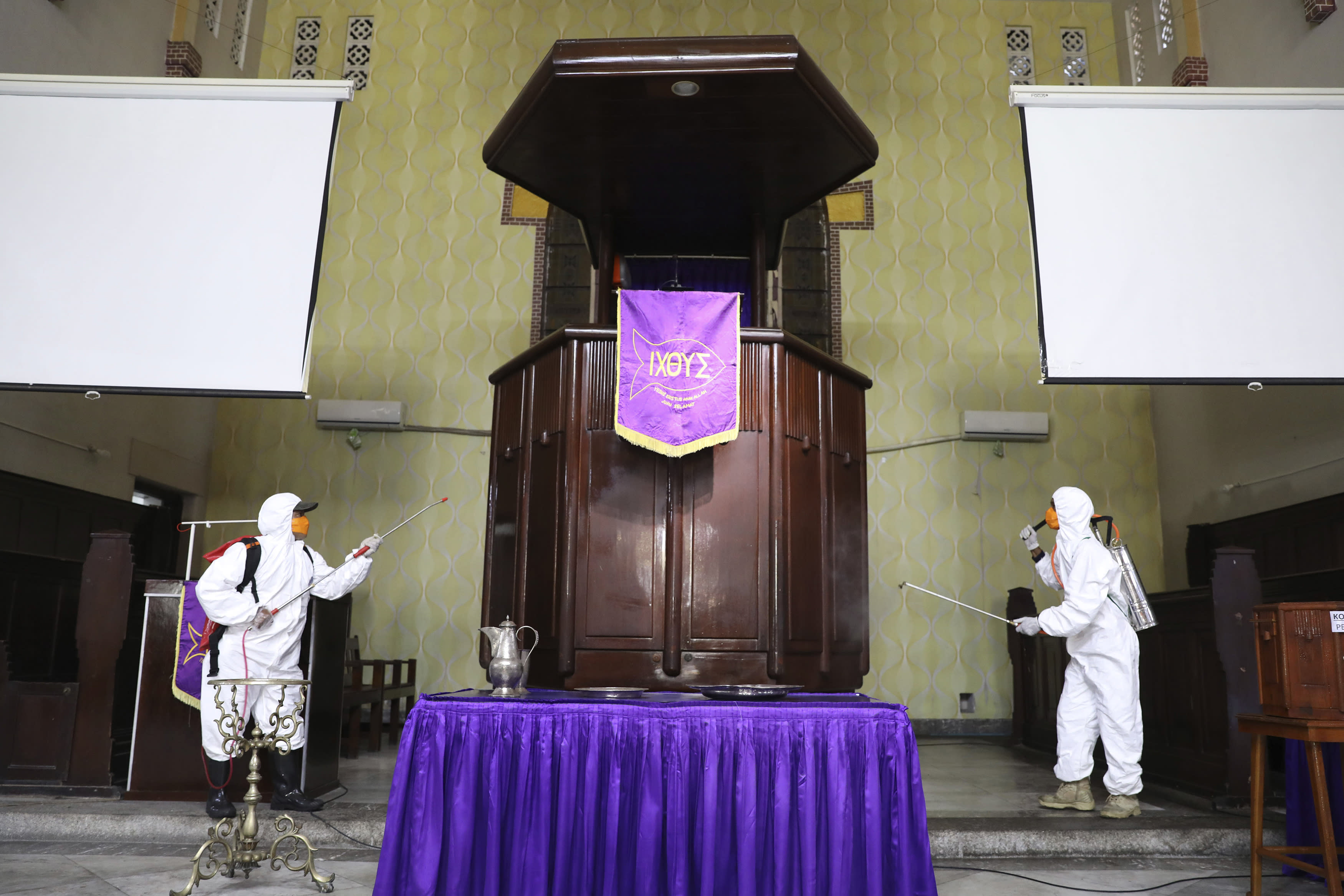 Workers of Disaster Mitigation Agency spray disinfectant inside a church amid fears of the new coronavirus outbreak in Surabaya, East Java, Indonesia, Wednesday, March 18, 2020. For most people, the new coronavirus causes only mild or moderate symptoms. For some it can cause more severe illness. (AP Photo/Trisnadi)
