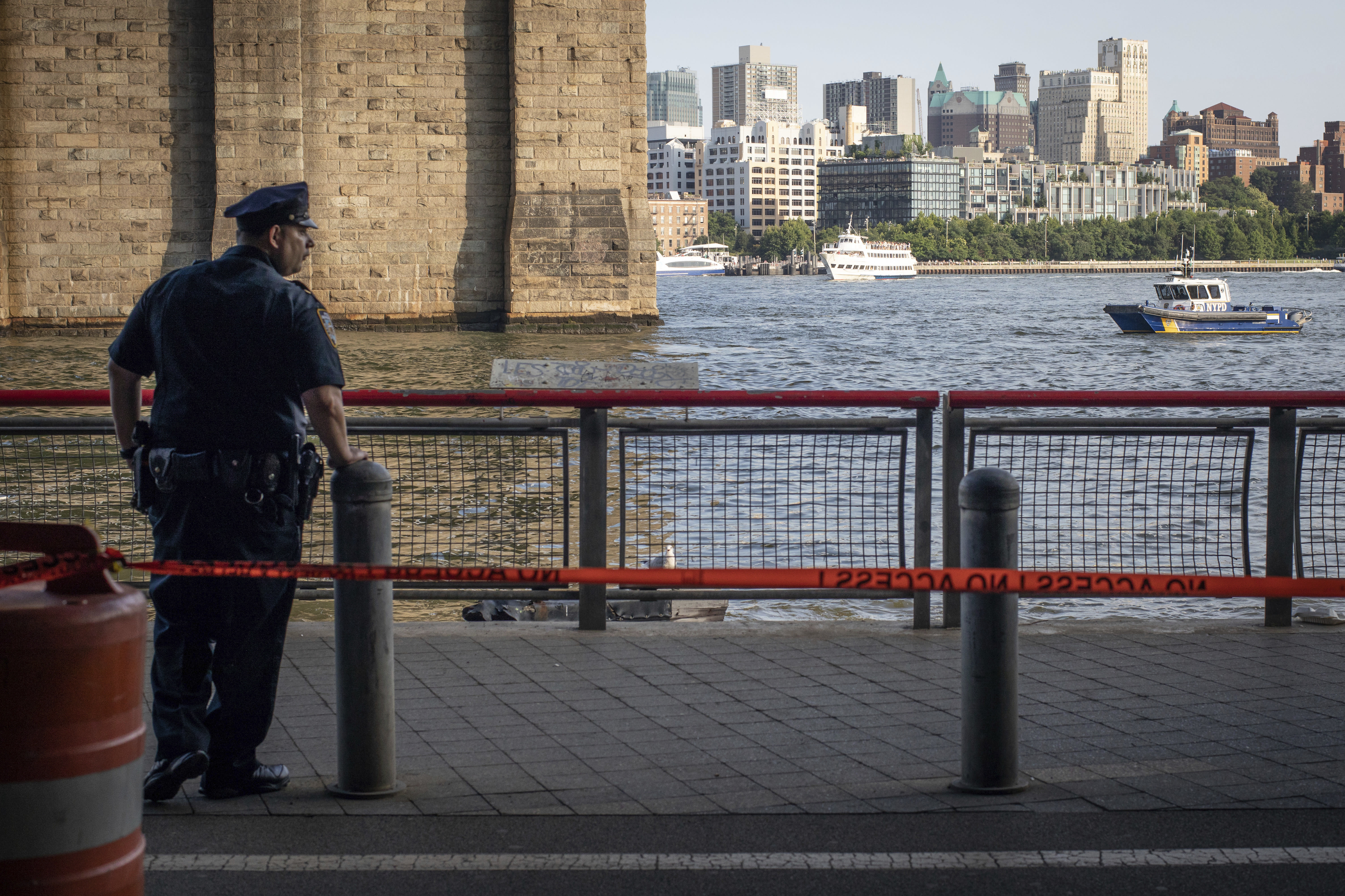 A New York Police Department officer stands guard as authorities investigate the death of a baby boy who was found floating in the water near the Brooklyn Bridge in Manhattan, on Sunday, Aug. 5, 2018, in New York. No parent or guardian was present at the scene and the child showed no signs of trauma, police said. The medical examiner will determine the exact cause of death. (AP Photo/Robert Bumsted)