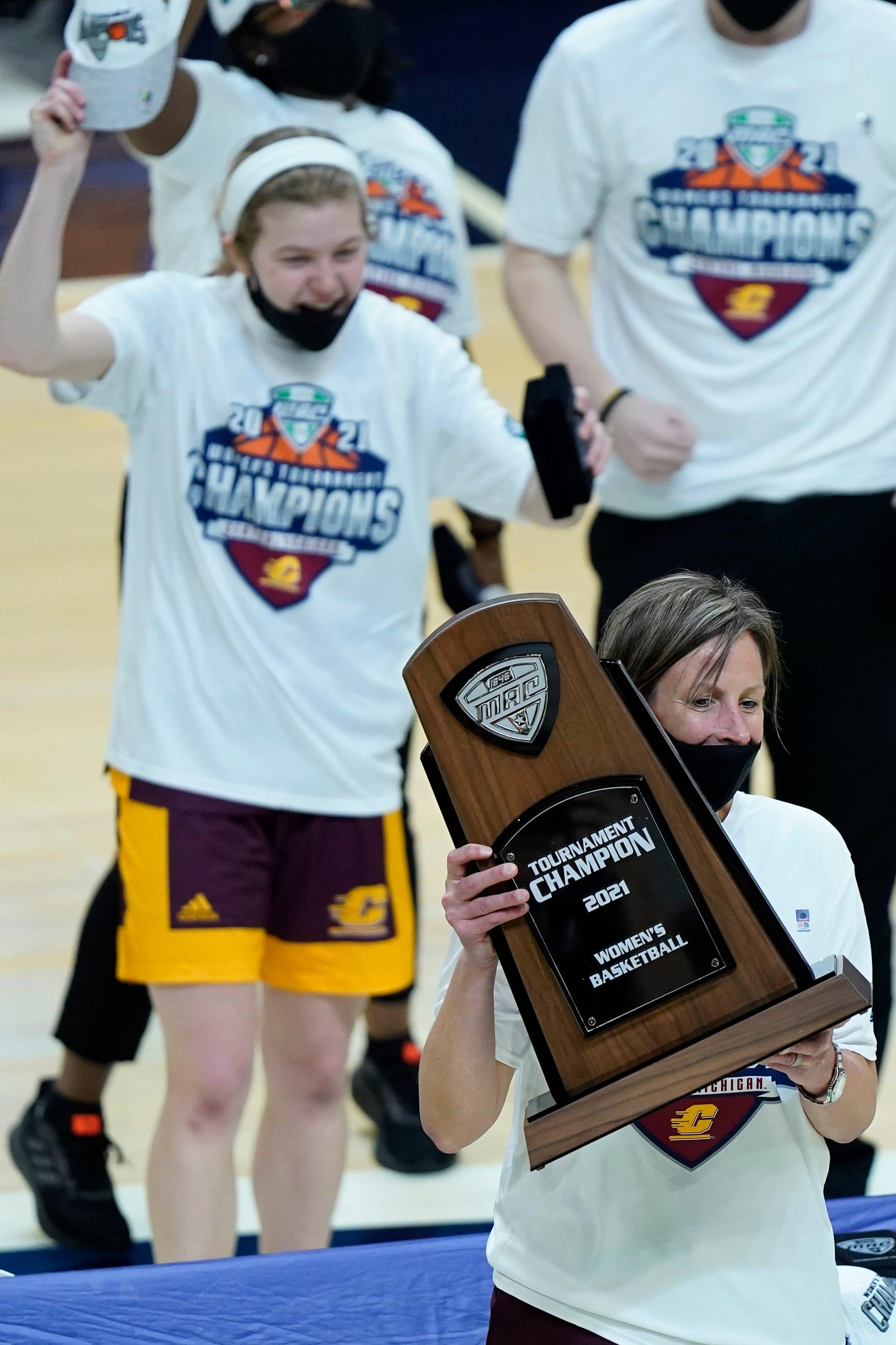 Central Michigan coach Heather Oesterle holds up the trophy after CMU defeated Bowling Green, 77-72, in the championship of the Mid-American Conference tournament on Saturday, March 13, 2021, in Cleveland.