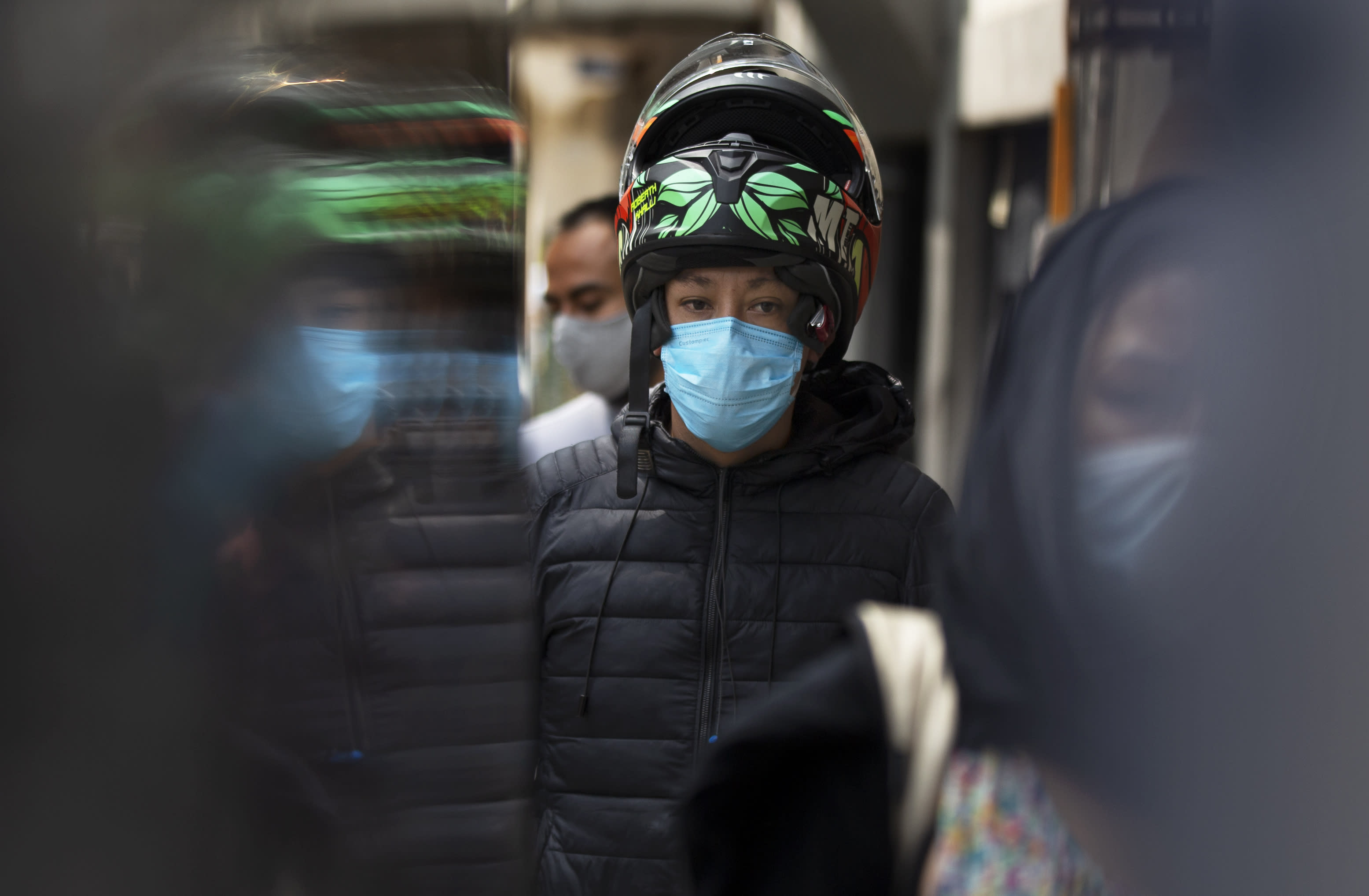 """A customer, wearing a protective face mask amid the new coronavirus pandemic, stands in line at stall selling """"torta de chilaquiles"""", in Mexico City, Saturday, Aug. 1, 2020. More than half of Mexicans work in the informal economy, which is believed to have shed many more jobs as the economic shutdown caused by the COVID-19 pandemic has driven the country deeper into a recession. (AP Photo/Marco Ugarte)"""