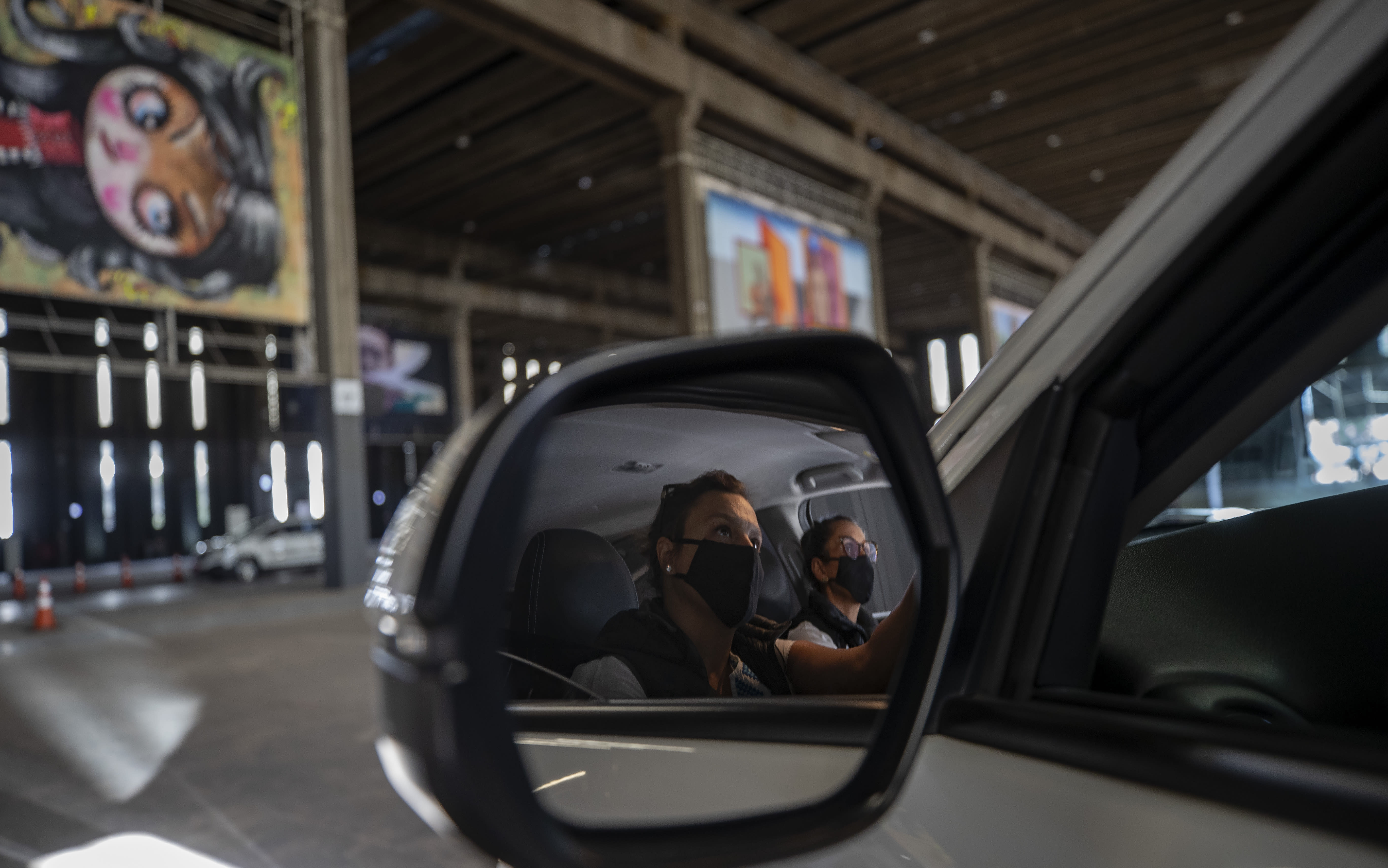 Visitors take in an art exhibit from inside a car as they drive through a warehouse displaying paintings and photos in Sao Paulo, Brazil, Friday, July 24, 2020, amid the new coronavirus pandemic. Galleries, cinemas, theaters and museums are closed due to the restrictive measures to avoid the spread of COVID-19, but a group of artists and a curator found a way to overcome the restrictions to share their art with the residents of Brazil's largest city. (AP Photo/Andre Penner)