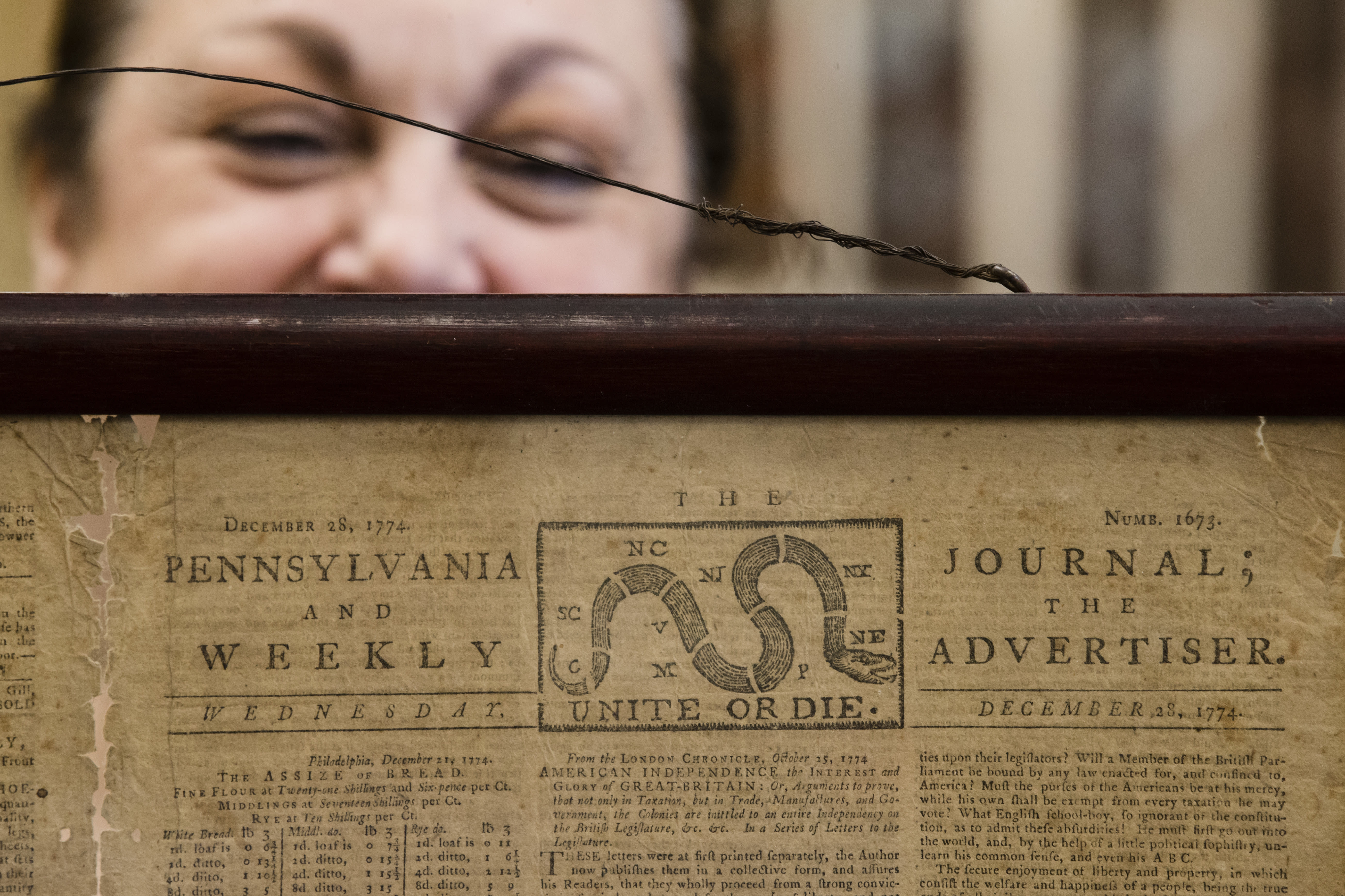 """Heather Randall displays a Dec. 28, 1774 Pennsylvania Journal and the Weekly Advertiser at the Goodwill Industries in Bellmawr, N.J., Thursday, Oct. 25, 2018. A quick eye by Goodwill workers in southern New Jersey turned up an original 1774 Philadelphia newspaper with an iconic """"Unite or Die"""" masthead. (AP Photo/Matt Rourke)"""