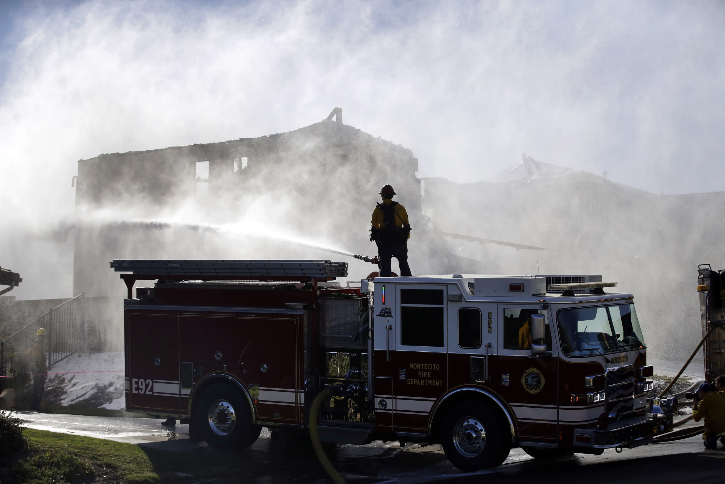 A firefighter tries to put out a residence fire caused by a wildfire from atop a fire truck Friday, Oct. 25, 2019, in Santa Clarita, Calif. An estimated 50,000 people were under evacuation orders in the Santa Clarita area north of Los Angeles as hot, dry Santa Ana winds howling at up to 50 mph (80 kph) drove the flames into neighborhoods(AP Photo/Marcio Jose Sanchez)