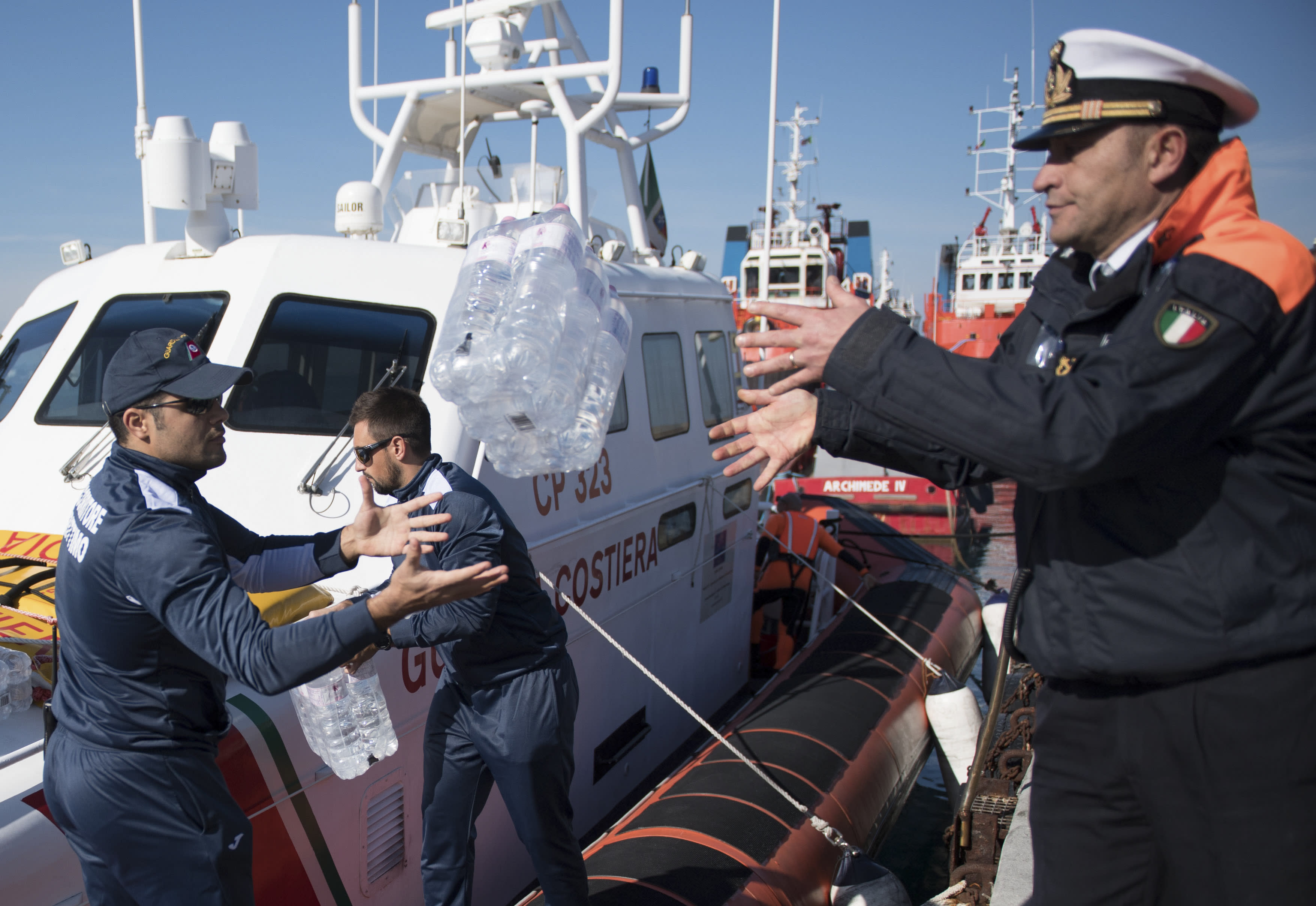 Water is unloaded from a coastguard boat to the German humanitarian group's rescue boat Sea Watch 3, as food and blankets for the cold were delivered, off the coast of Syracuse, Italy, Sunday, Jan. 27, 2019. The Italian coast guard is bringing socks, shoes, bread and fruit to 47 migrants who have been stranded at sea for nine days aboard a German ship. (AP Photo/Salvatore Cavalli)