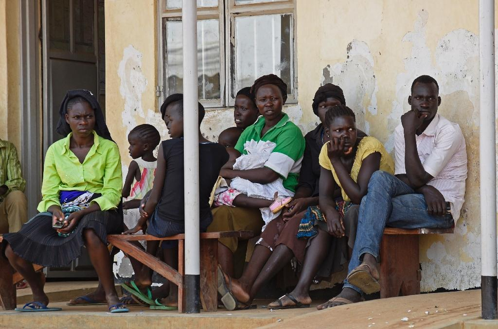 Newly arrived refugees from South Sudan wait outside the Elegu Collection Centre in Amuru on July 13, 2016