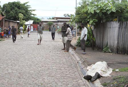 Residents look at the covered body of an unidentified man killed during gunfire, in the Nyakabiga neighbourhood of Burundi's capital Bujumbura, December 12, 2015. REUTERS/Jean Pierre Aime Harerimana