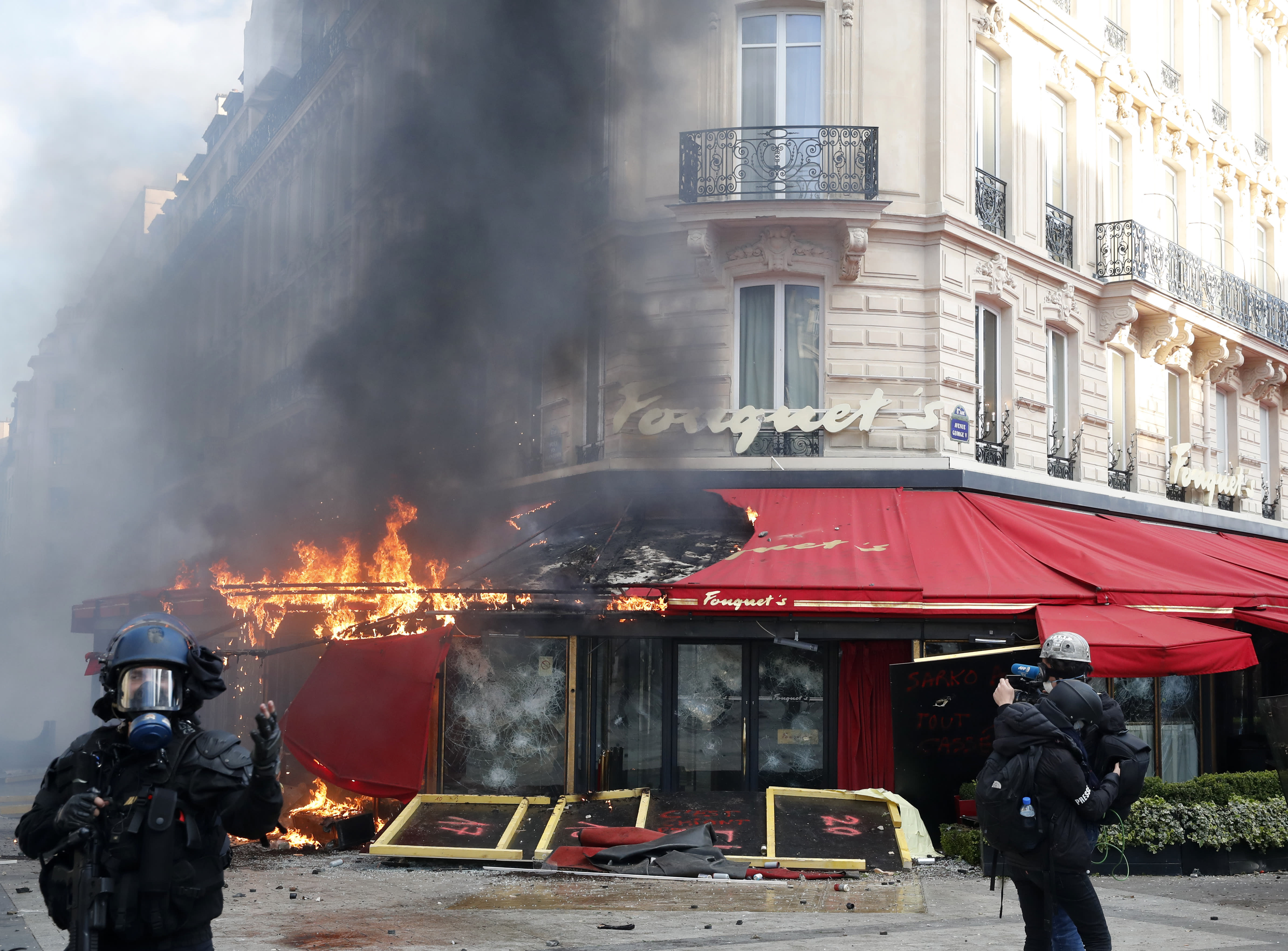 Paris famed restaurant Fouquet's burns on the Champs Elysees avenue during a yellow vests demonstration Saturday, March 16, 2019 in Paris. Paris police say more than 100 people have been arrested amid rioting in the French capital by yellow vest protesters and clashes with police. They set life-threatening fires, smashed up luxury stores and clashed with police firing tear gas and water cannon (AP Photo/Christophe Ena)
