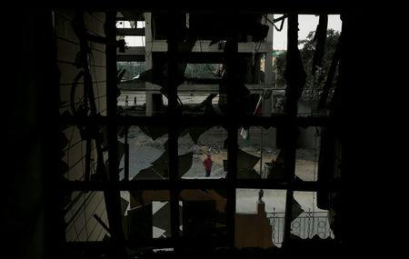 A Palestinian man looks at the Ministry of Religious Affairs that was damaged by Israeli air strikes in Gaza City July 15, 2018. REUTERS/Suhaib Salem