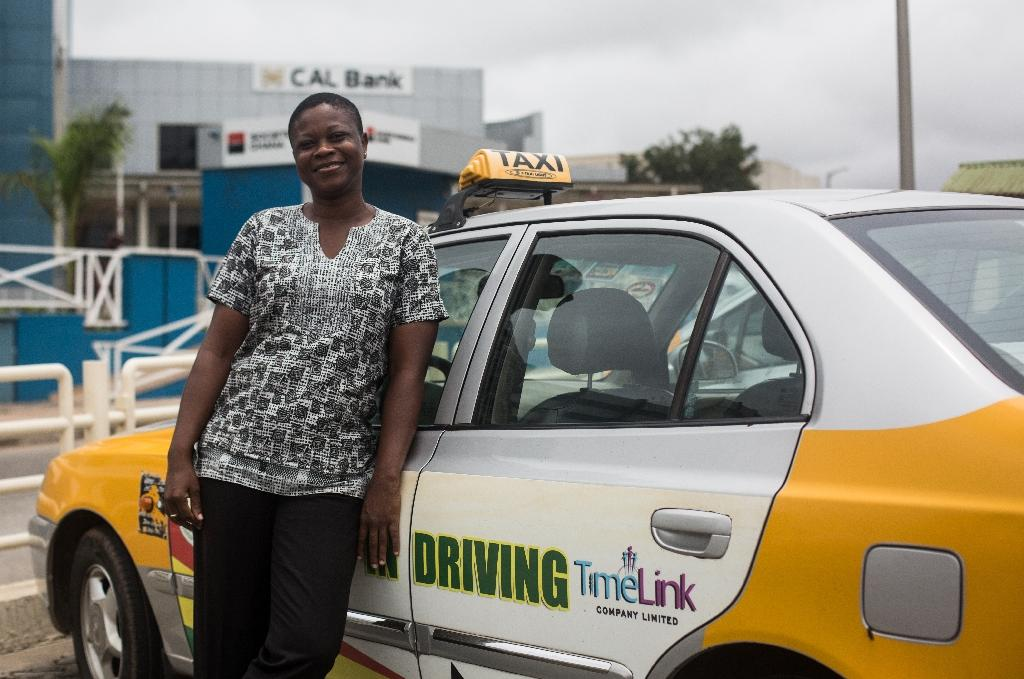 Nyador, one of the few professional female taxi drivers operating in the city, poses for a photograph next to her cab in Accra (AFP Photo/Ruth McDowall)