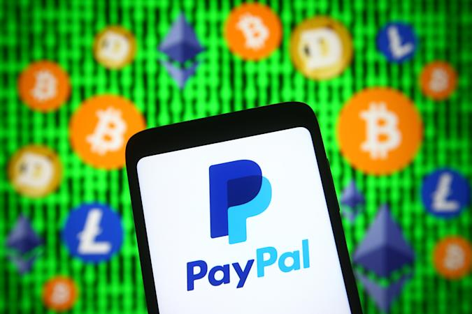 UKRAINE - 2021/04/30: In this photo illustration, PayPal logo is seen displayed on a smartphone screen in front of cryptocurrency signs. (Photo Illustration by Pavlo Gonchar/SOPA Images/LightRocket via Getty Images)
