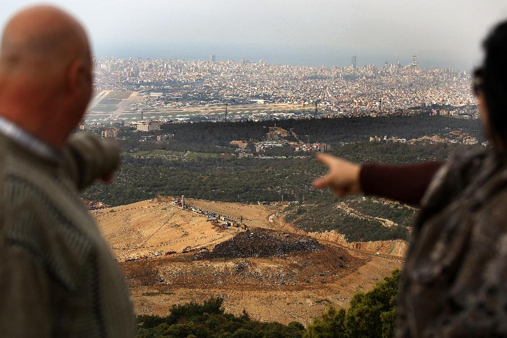 A Lebanese couple point from their balcony in the village of Baawarta at trucks unloading garbage at the Naameh landfill, south of Beirut, on March 30, 2016 (AFP Photo/Patrick Baz)