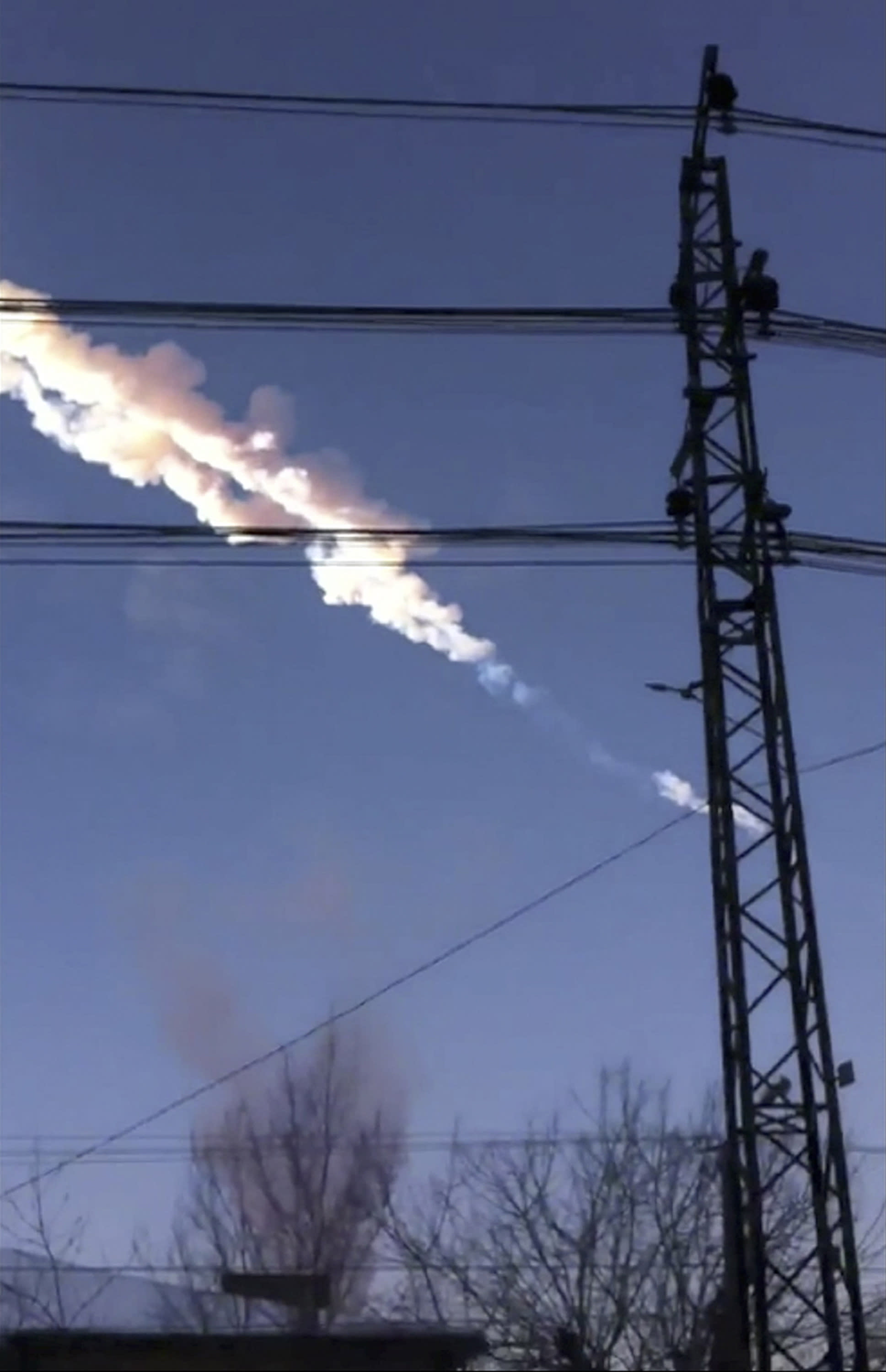 In this photo taken with a mobile phone camera, a meteorite contrail is seen in Chelyabinsk region on Friday, Feb. 15, 2013. A meteor streaked across the sky of Russia's Ural Mountains on Friday morning, causing sharp explosions and reportedly injuring around 100 people, including many hurt by broken glass. (AP Photo/Sergey Hametov)