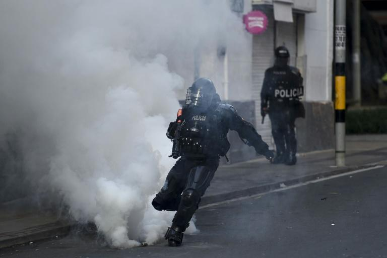 A riot police officer kicks a tear gas canister during protests against police brutality in Medellin, Colombia