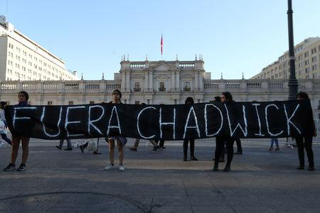 """Indigenous Mapuche activists hold a banner, which reads: """"Chadwick (Interior Minister) Out"""", outside the government house during a protest demanding justice for Camilo Catrillanca, an indigenous Mapuche man who was shot in the head during a police operation, in Santiago, December 20, 2018. REUTERS/Ivan Alvarado"""