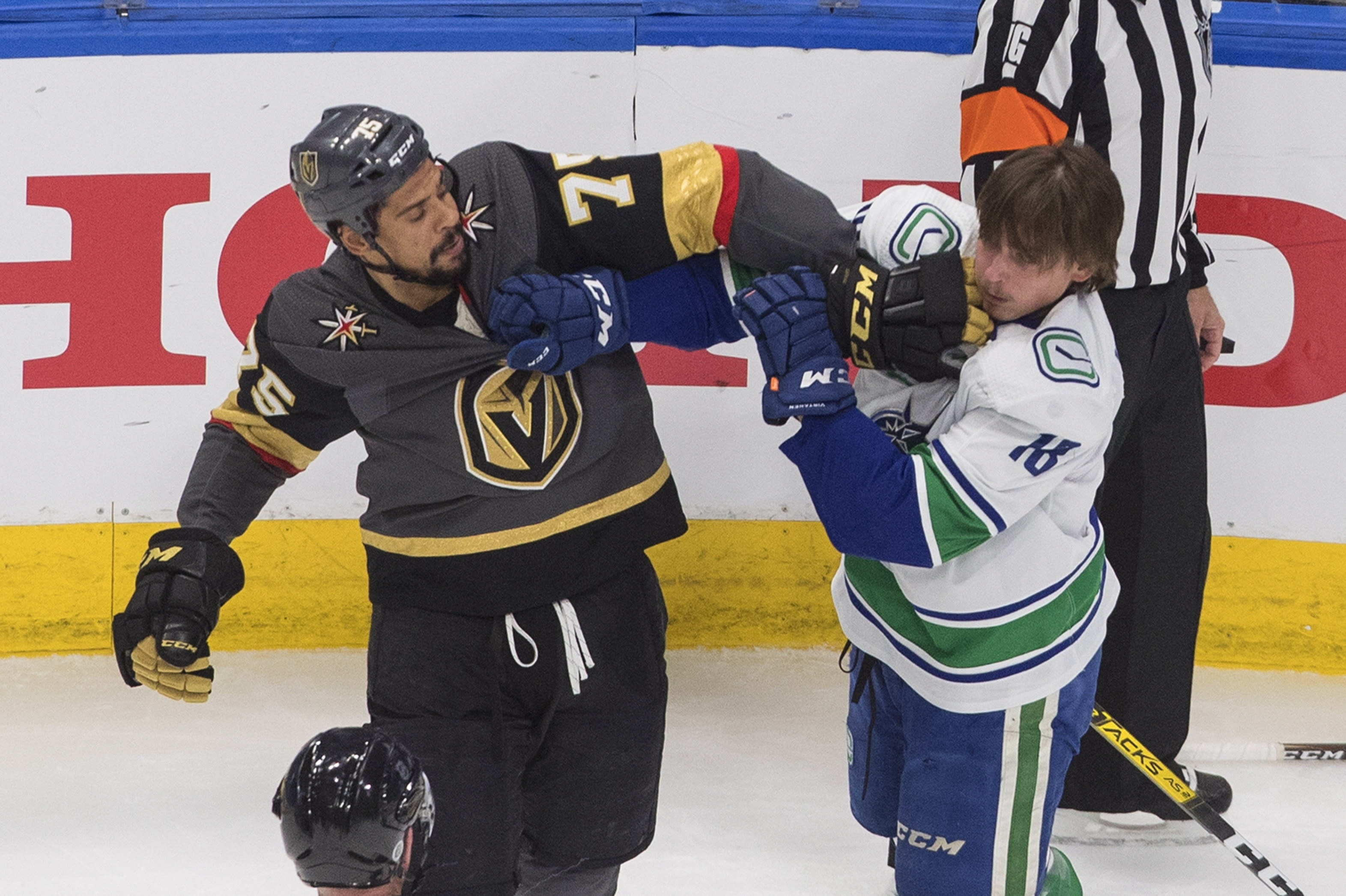 Vancouver Canucks' Jake Virtanen (18) and Vegas Golden Knights' Ryan Reaves (75) rough it up during the first period of Game 7 of an NHL hockey second-round playoff series, Friday, Sept. 4, 2020, in Edmonton, Alberta. (Jason Franson/The Canadian Press via AP)