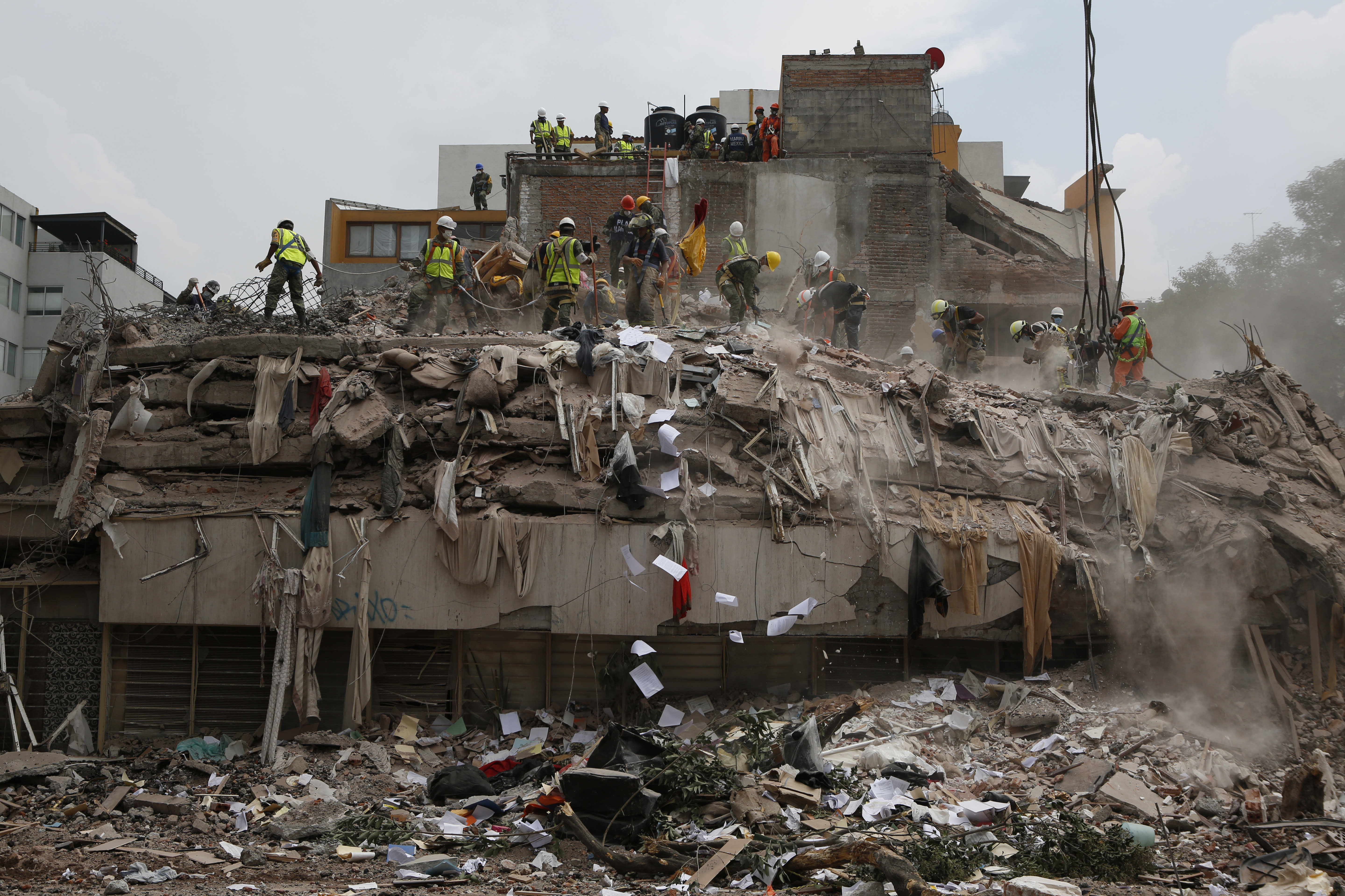 FILE - In this Sept. 25, 2017, file photo, workers shovel papers and debris off the top of the rubble of a building that collapsed in last week's 7.1 magnitude earthquake, at the corner of Gabriel Mancera and Escocia streets in the Del Valle neighborhood of Mexico City. The virus outbreak is compromising the ability of nations to prepare for natural disasters and deal with the aftermath. Every year, the world contends with devastating typhoons, wildfires, tsunamis and earthquakes. (AP Photo/Rebecca Blackwell, File)