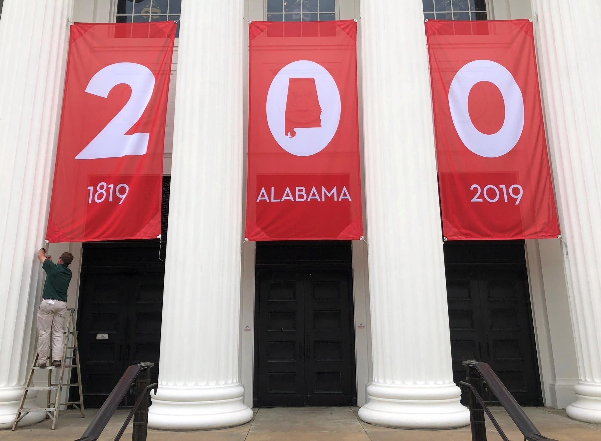 """FILE - In this Feb. 28, 2019 file photo a worker adjusts a banner celebrating Alabama's bicentennial outside the Department of Archives and History in Montgomery, Ala. Leaders in Alabama are confronting the legacy of what might be the grandest Confederate memorial of all: the state's Department of Archives and History. During the current national reckoning over race, its current leaders acknowledged the department once played a role in systemic racism by promoting """"lost cause"""" narrative of Civil War history that was favored by some whites and all but excluding Blacks. (AP Photo/Jay Reeves, File)"""
