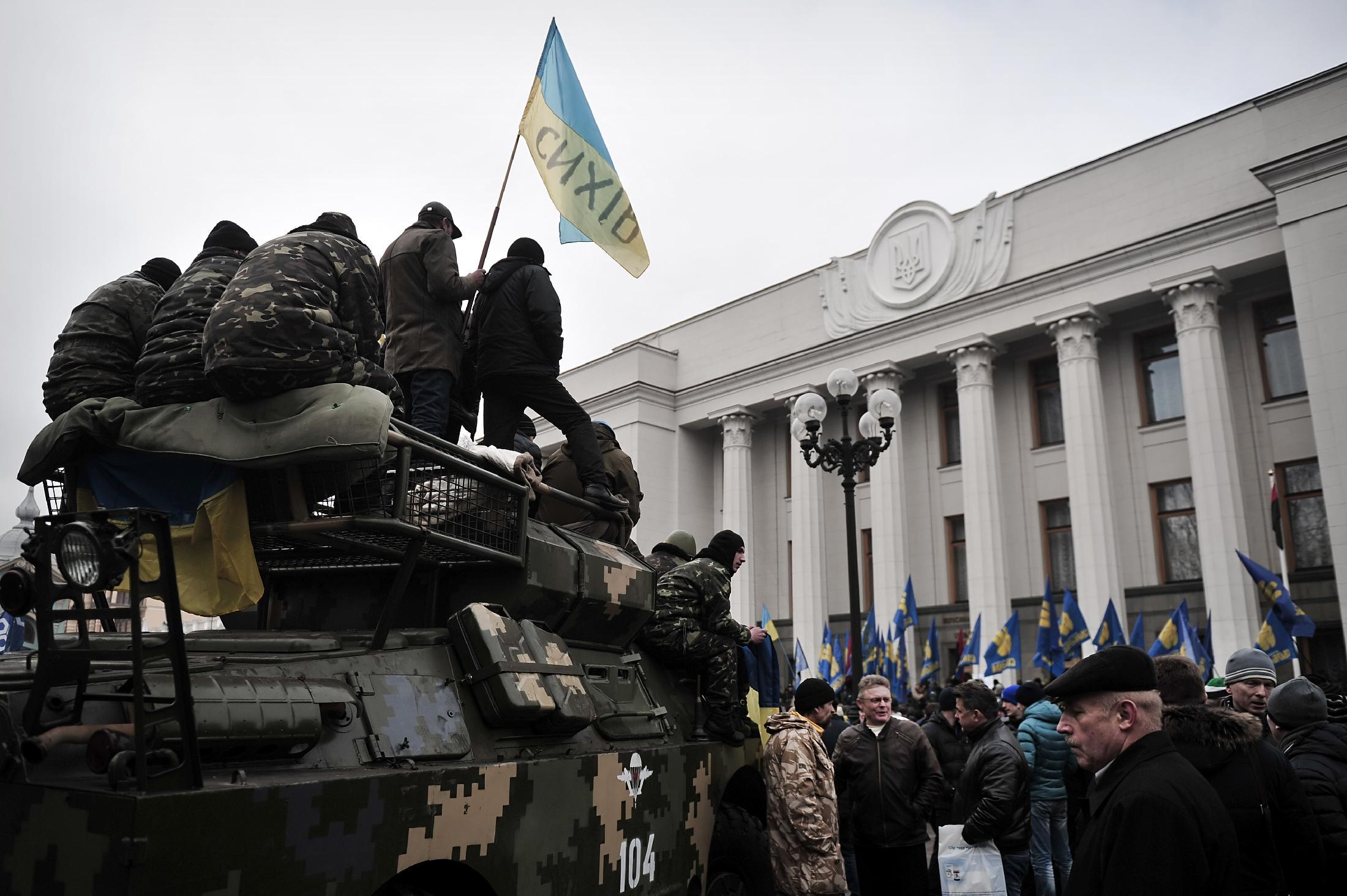 Maidan self-defence activists sit on an armoured vehicle in front of the parliament in central Kiev on February 27, 2014 (AFP Photo/Louisa Gouliamaki)