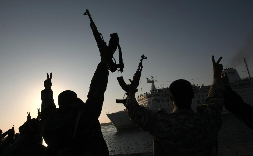 Rebel fighters hold their weapons aloft to welcome a Turkish ship arriving from Misrata to the port of Benghazi to evacuate the wounded on April 3, 2011 (AFP Photo/Mahmud Hams)
