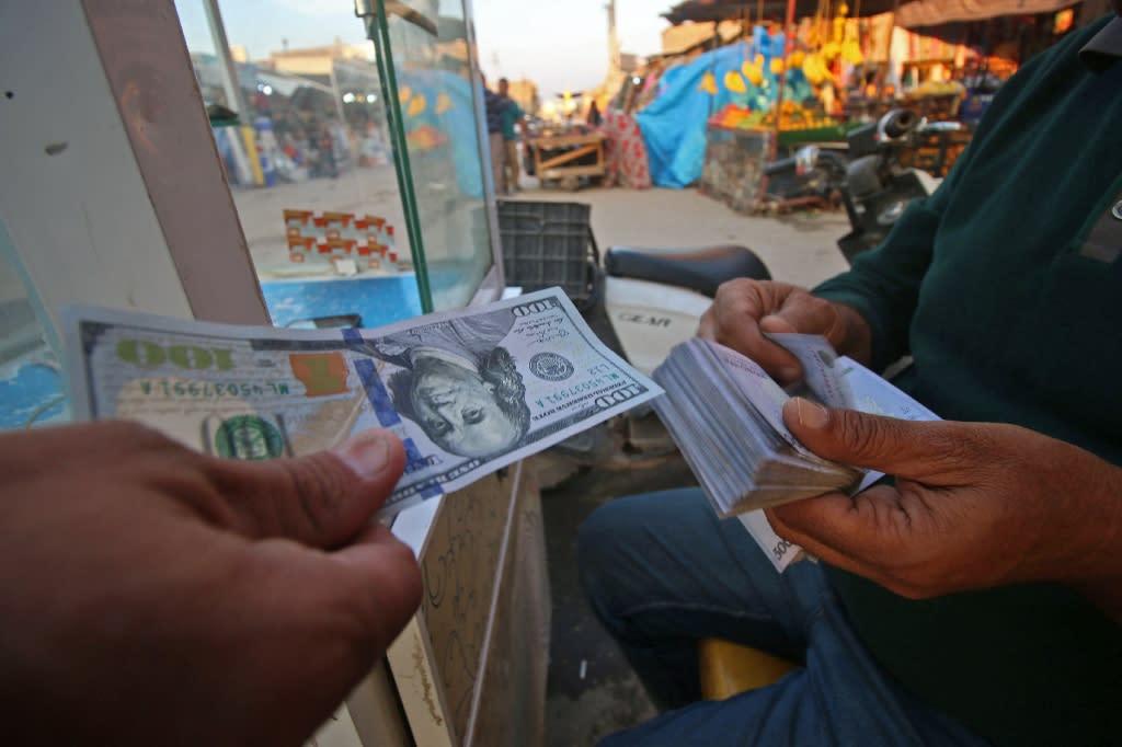 An Iraqi man changes US dollars for Iranian rials in Basra on November 6, 2018 (AFP Photo/Haidar MOHAMMED ALI)