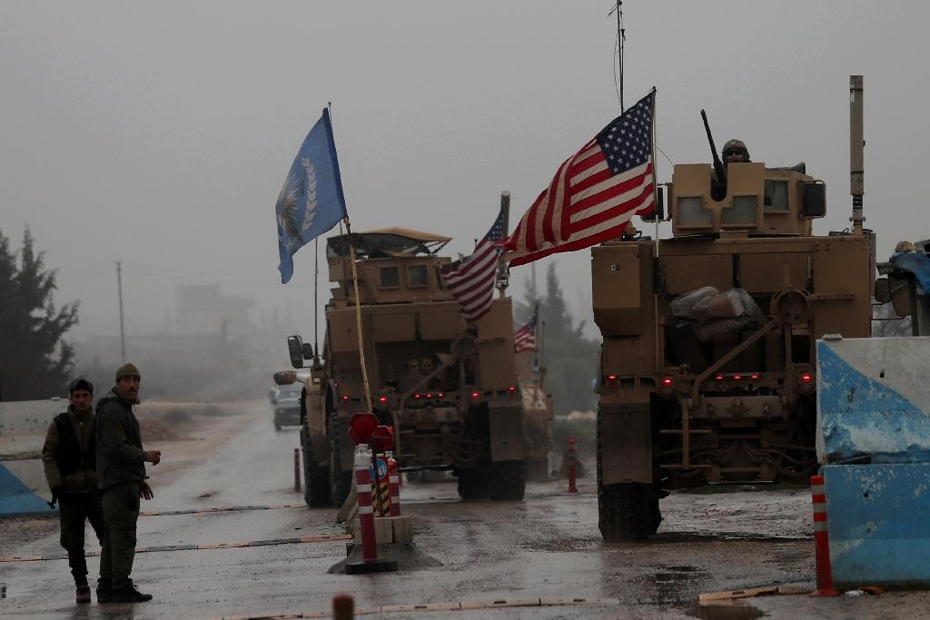 A line of US military vehicles drive through a checkpoint of the Internal Security Forces in Manbij as they head to their base on the outskirts of the northern Syrian city on December 30, 2018