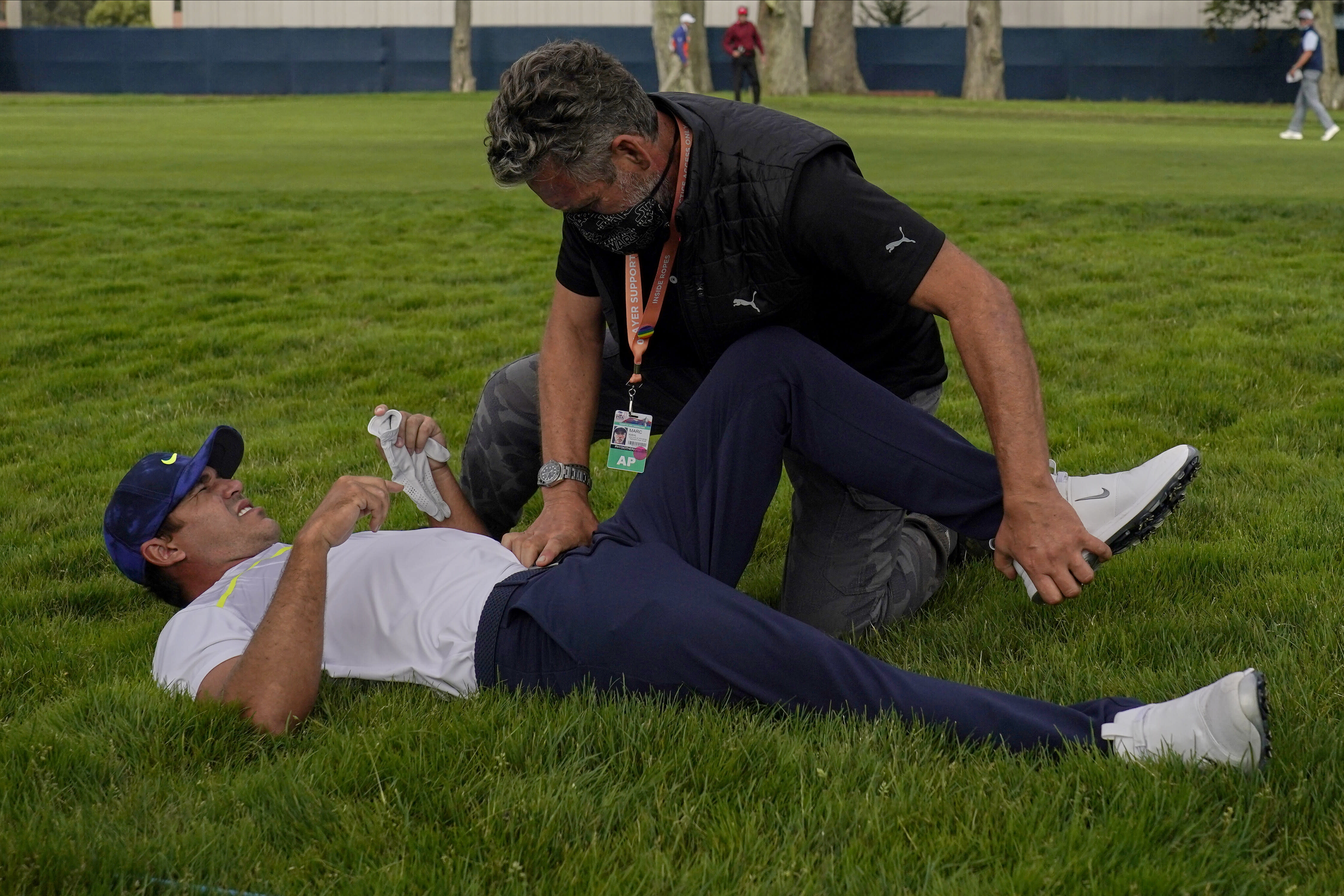 Brooks Koepka gets treated for an injury on the 12th hole during the second round of the PGA Championship golf tournament at TPC Harding Park Friday, Aug. 7, 2020, in San Francisco. (AP Photo/Jeff Chiu)