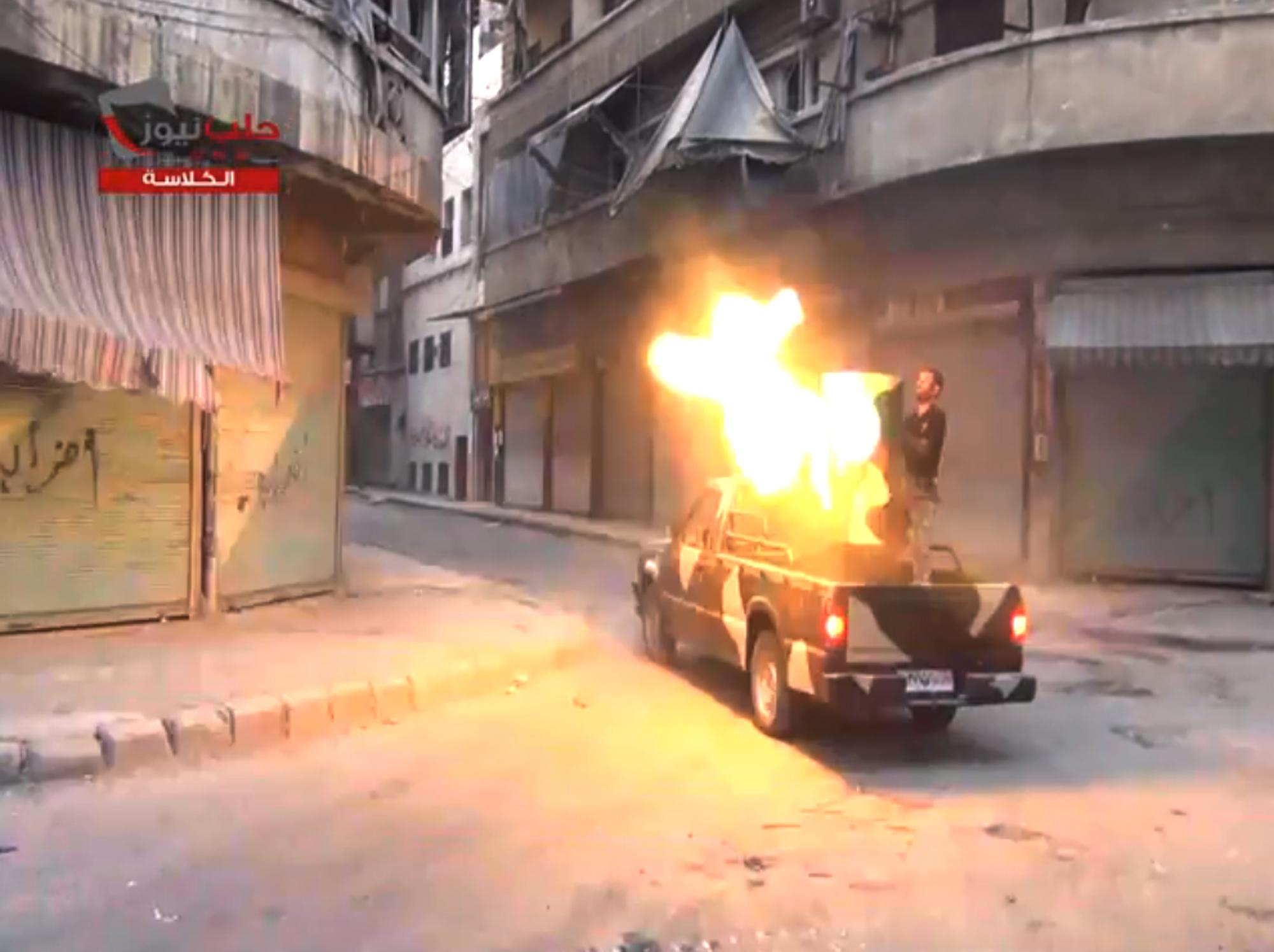 """In this image taken from video obtained from the Shaam News Network, which has been authenticated based on its contents and other AP reporting, fighters from the Free Syrian Army targets one of the bastions of the regime's forces in Aleppo, Syria, Monday July 22, 2013. Syrian rebels seized a strategic village on the edge of the northern city of Aleppo on Monday, activists said, just hours after other opposition fighters sustained some of their heaviest losses in months in battles to the south near the capital, Damascus. Logo reads, """"Aleppo News – al-Kalasa."""" (AP Photo/Shaam News Network via AP video)"""