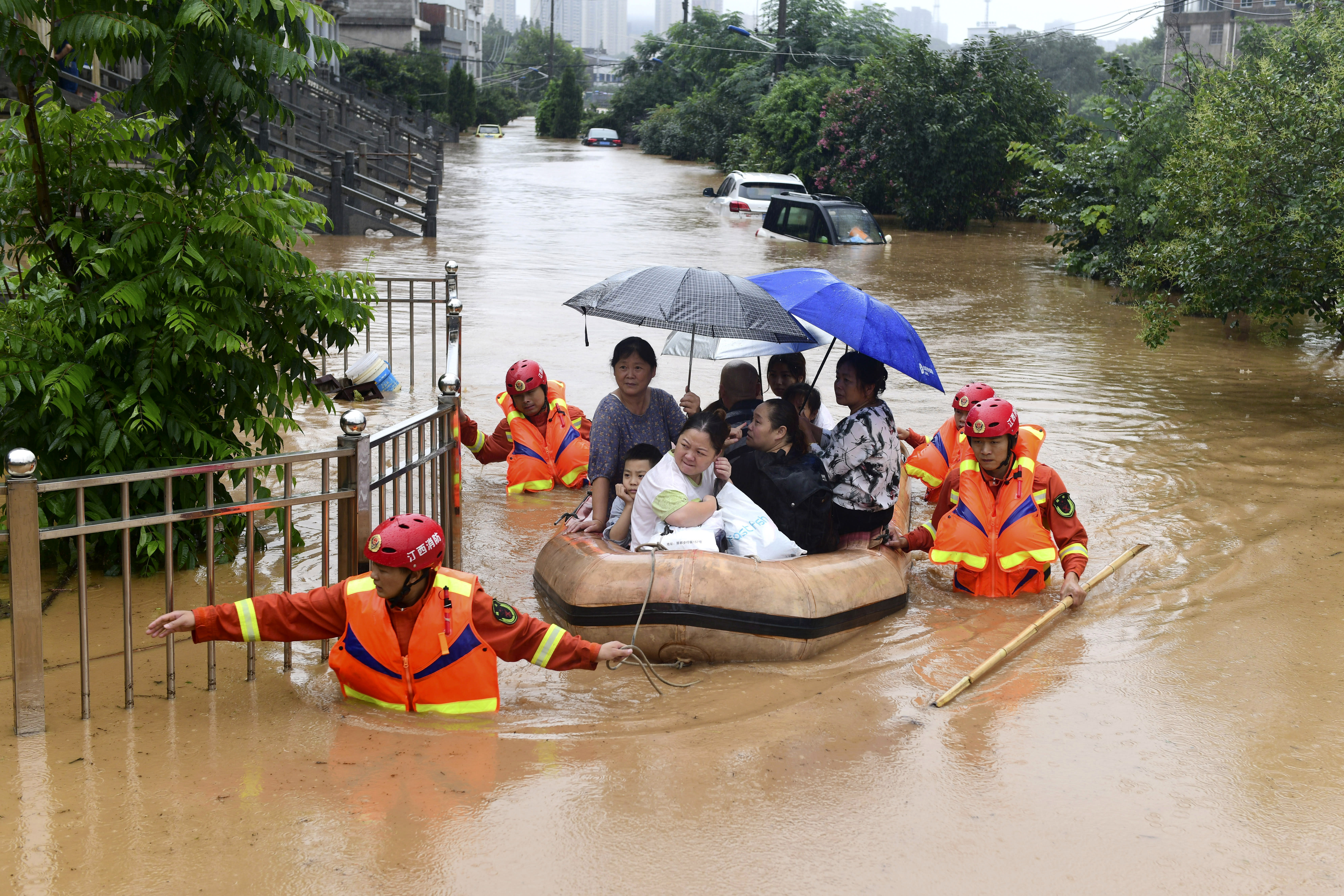 Rescuers evacuate residents on a raft through flood waters in Jiujiang in central China's Jiangxi province Wednesday, July 8, 2020. Rescuers in central China were searching Wednesday for people left missing in a landslide triggered amid widespread flooding across much of the country. (Chinatopix Via AP)