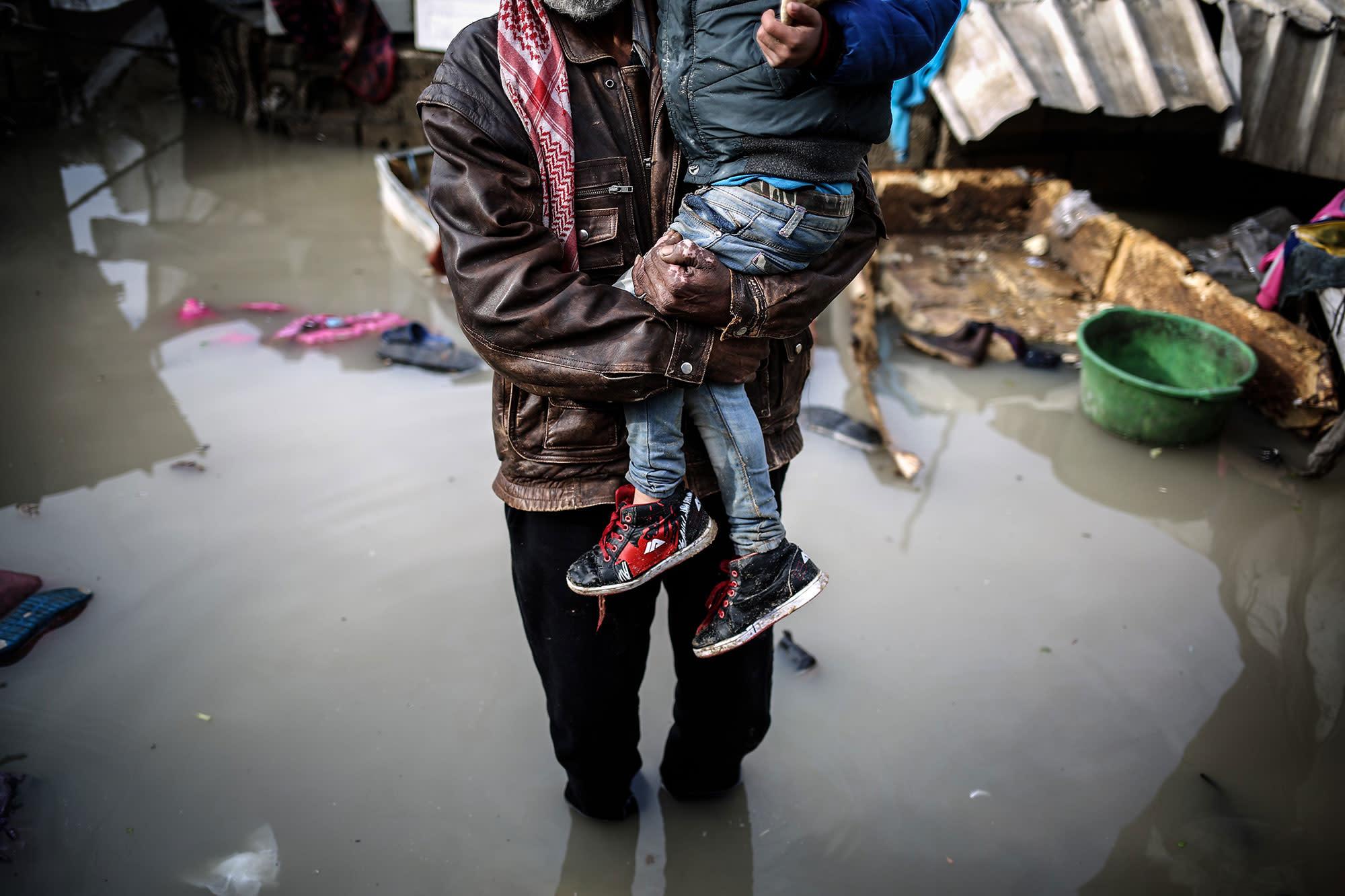 <p>A man with a boy walks through floodwater after heavy rainfall hit Gaza district of al-Saftawi, Gaza on February 16, 2017. (Ali Jadallah/Anadolu Agency/Getty Images) </p>
